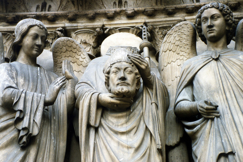 The angel is standing to the side of Saint Denis (the Headless Saint), who was tortured and decapitated by the Roman military around 273