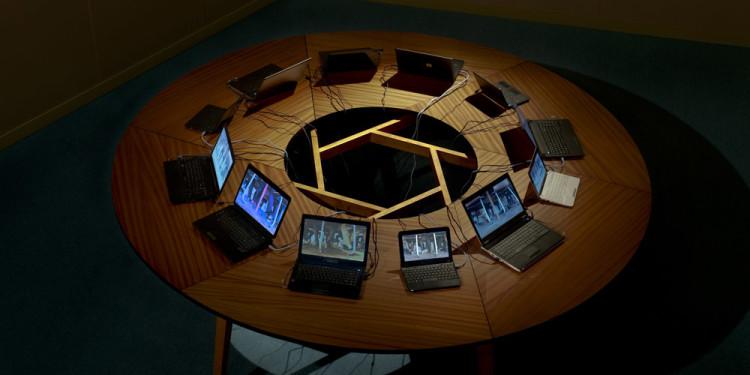 """Sigalit Landau Salt Bridge Summit, 2011 12 Channels Video & sound installation, 300 cm round wooden table, 12 laptops, with """"Laces"""" video. Installation view, Israeli Pavilion, 54th Venice Biennale, Venice, 2011 © Sigalit Landau Courtesy the artist and kamel mennour, Paris"""