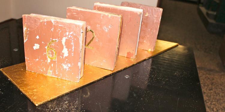 installazione di Giobatta Meneguzzo, finestrelle di legno, staccate dalle porte carcerarie ed allineate su una lamina dorata