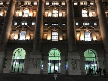 Imponente facciata illuminata di Palazzo Mezzanotte, sede storica di Borsa Italiana, Milano