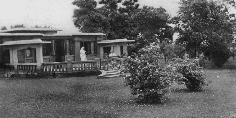 Rabindranath works on the terrace of Punashcha, Santiniketan, as Mrs Chaudhury(?) takes a photograph of him, by Shambhu Shaha. From Faces & Places of Visva-Bharati: A Collection of Photographs, by Shambhu Shaha, 2nd edn., Visva-Bharati Publishing Department, Kolkata, 2008. Rabindra Bhavana Acc. No. SS115.